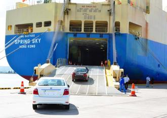 チャーター船に積み込まれるスカイレンタカーのレンタアップ車=24日、中城湾港