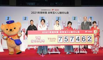 お年玉付き年賀はがきと切手の抽せん会で、1等の当せん番号を手に写真に納まるゲストら。右から2人目はロバート・キャンベルさん=17日午後、東京・丸の内のJPタワー