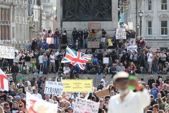 19日、ロンドン中心部で行われた新型コロナウイルス対策の規制再強化に抗議するデモ(英PA通信=共同)