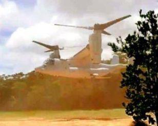 砂ぼこりを巻き上げながら着陸するオスプレイ=14日午後2時前、国頭村安波(読者提供)