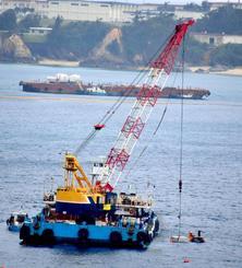 次々と海中に投下される汚濁防止膜固定用のコンクリートブロック=31日午後3時14分、名護市・大浦湾(城間陽介撮影)