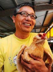 健康志向でアローカナの飼育に取り組む上原肇さん=11日、糸満市北波平の上原養鶏場
