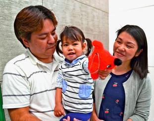 元気な姿で帰国し、報道陣に笑顔を見せる翁長希羽ちゃん(中央)と父・司さん(左)、母・涼子さん=20日、成田空港