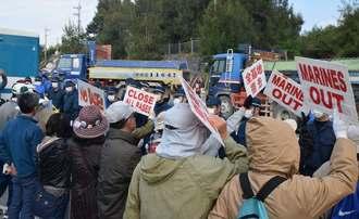 機動隊が市民を囲い込む中、米軍キャンプ・シュワブ内に入る工事関係車両=9日午前9時、名護市辺野古