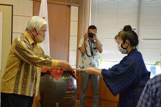 新里米吉県議会議長(左)に要請書を手渡す沖縄全戦没者追悼式のあり方を考える県民の会の知念ウシさん=1日、県議会