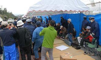 三線演奏の雨よけのために建てられたテントの足を持ち上げ、撤去する機動隊員ら=4日午前9時23分、名護市辺野古の米軍キャンプ・シュワブゲート前