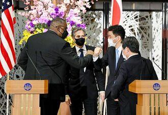 日米の外務・防衛担当閣僚による安全保障協議委員会後の共同記者会見を終え、オースティン米国防長官(左端)と肘でタッチを交わす岸防衛相。奥はブリンケン米国務長官、右端は茂木外相=16日午後、東京都港区の飯倉公館(代表撮影)