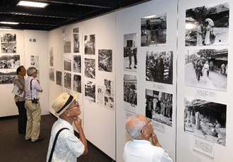 1935年の沖縄を写した写真に見入る来場者=21日、那覇市久茂地・タイムスギャラリー