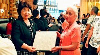 記念品を交換する比嘉京子議員(左)と神山初子さん=カナダ・トロントの居酒屋りょう次