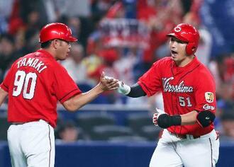 9回、勝ち越し本塁打を放ち、玉木コーチ(左)とタッチする広島・鈴木=ナゴヤドーム