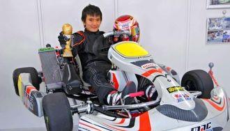 大会で運転したレーシングカーに乗り、優勝トロフィーを見せる平良響君=読谷村・ククル読谷サーキット