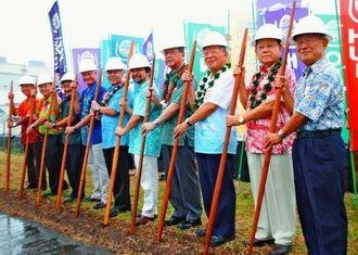 ハワイ先住民の農耕具「オオ」を大地に刺して起工式を執り行う県人会関係者ら=11日、ハワイ州ワイパフ(日本時間12日、又吉俊充撮影)