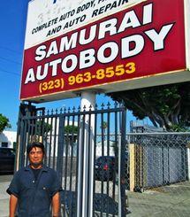 経営する「サムライオートボディ」の看板の前に立つ金城剛さん=ガーデナ市