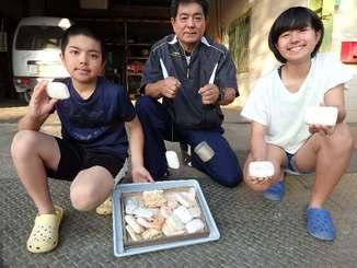 「ガラサーのジンブンに勝った」と話す宮城伸さん(中央)と、新たに見つかったせっけんを手にする星琉斗(せると)さん(左)、南美桜(なみか)さん=22日、名護市大西・名護工業