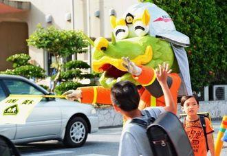 登校する小学生に手を振りながら、交通安全指導をするはりゅうくん=那覇市東町