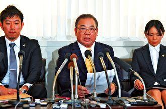 県教員採用試験への介入を否定し、前教育長を告訴したことを発表する安慶田光男前副知事(中央)=26日午前、県庁記者クラブ