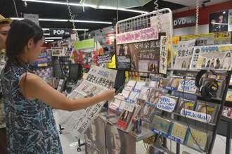 特設コーナーで号外を手に取る安室奈美恵さんの女性ファン=24日、那覇市久茂地・タワーレコード那覇リウボウ店
