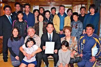 合格者名簿を手にする照屋将貴さん(前列中央)と合格を喜ぶ親族=14日、名護市