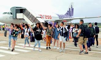 香港発の初便で到着し、笑顔で手を振る観光客ら=19日、宮古島市・下地島空港
