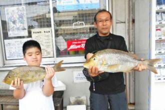 糸満海岸で60センチ、2・82キロと53・3センチ、2・04キロのタマンを釣った粟国広誠さん(左)=5月31日