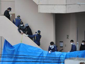 容体者が住むアパートの家宅捜索で、階段に残る血痕らしきものなどを調べる捜査員=11日午後4時30分ごろ、石垣市内
