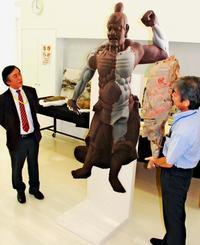 高さ約2メートルの仁王像(阿形)の実物大模像の写真パネル。パネル右側に掲げられた木製片は同像の残欠部分=15日、那覇市おもろまち、県立博物館・美術館