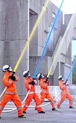 カラフルな水を放水する隊員=6日、南城市玉城・島尻消防組合