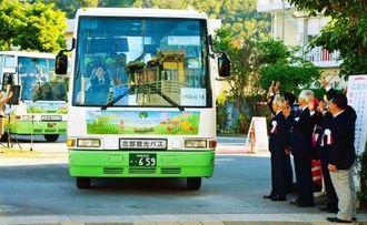 出発する「やんばる周遊バス」と手を振って見送る関係者=19日、名護市
