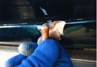 車両の左側面にあった傷と、そばに落ちていた銃弾らしき物(恩納村役場提供)