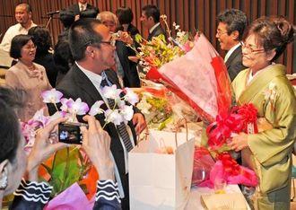 花束を受け取り、満面の笑みを浮かべる受賞者(右)=26日午後、那覇市久茂地・タイムスホール