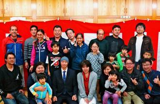 普天間三区の「成人祝い」で祝福を受ける二上秀文さん(前列左から4人目)と渡名喜庸松自治会長(後列左から4人目)=7日、宜野湾市、普天間三区公民館
