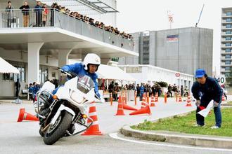 設置されたカラーコーンを避けながら走行する白バイ隊員=日、豊見城市・県警察運転免許センター