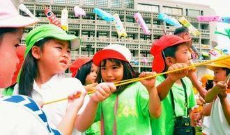 【よいしょ!】ひもを引っ張り、こいのぼりを揚げる子どもたち=4月27日、南風原町役場