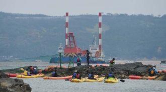 作業船の動きを警戒する抗議のカヌー隊(手前)=16日午前9時52分、名護市辺野古崎