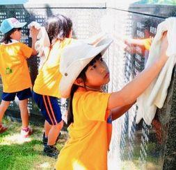 刻銘版をタオルで磨く小学生ら=18日午前10時、糸満市摩文仁・平和祈念公園