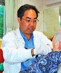 「よく頑張ってる。もう少し」と声を掛けながら治療にあたる我那覇生純さん=28日、熊本県阿蘇郡の高齢者福祉施設
