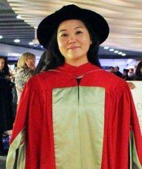 博士号取得を意味するマクギル大学伝統の薄緑のヘリの付いた赤色のガウンを着た仲田エミリーさん
