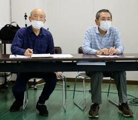 請求棄却を受け、記者会見する原告団長の河野哲雄さん(右)ら=14日午後、松江市