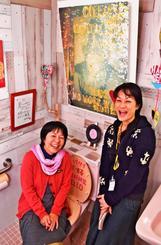 ギャラリーに変身したトイレ。石野裕子館長(左)、長谷川華乃子さんが中心に手掛けた=今帰仁村歴史文化センター