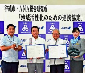 「地域活性化のための連携協定」を結んだ沖縄市の桑江朝千夫市長(左から2番目)とANA総合研究所の岡田晃社長(同3番目)ら=24日、沖縄市役所