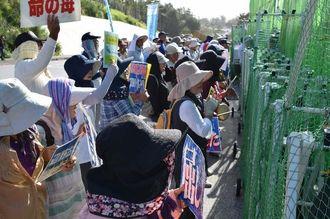 早朝行動で、基地に向かって「沖縄を返せ」を歌う県内各地の議員や市民ら=8日午前8時8分、名護市辺野古の米軍キャンプ・シュワブ前