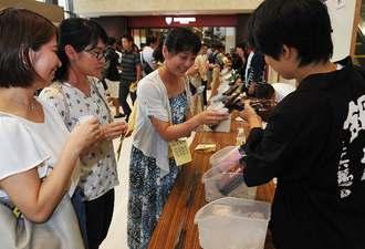 国内蔵元の日本酒を味わう来場客=6日、那覇市久茂地・タイムスビル