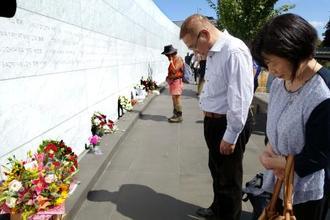 追悼式典に参列し、亡くなった堀田めぐみさんの名前が刻まれた慰霊碑に花を手向けた(右から)母聖子さんと父和夫さん=22日、ニュージーランド・クライストチャーチ(共同)