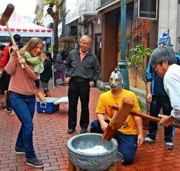 餅つきを楽しむ外国人と市内の住民ら=沖縄市・コザインターナショナルプラザ前