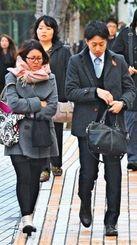 厳しい寒さの中、道行く人はマフラーやコートなどの厚着姿が目立った=25日午前8時23分、那覇市・パレットくもじ前