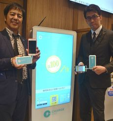「チャージスポット」の貸出機からバッテリーを取り出してみせる琉球銀行の伊禮真メディア戦略室長(左)と志良堂猛史IT・チャネル戦略室調査役=26日、国際通りの琉銀イチバンジャー出張所
