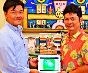 中国人向けのスマートフォン決済システムを導入する高倉総支配人(右)と倉岡代表社員=4日、那覇市の同ホテル