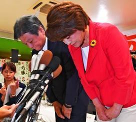 相手候補の当選確実のテレビ速報を受け、夫の昇さん(左)と共に支援者に頭を下げる島尻安伊子さん=21日午後8時13分、沖縄市中央の選挙事務所(国吉聡志撮影)