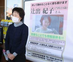 情報提供を呼び掛けるポスターの前で取材に応じる、辻出紀子さんの母美千代さん=24日午後、三重県伊勢市