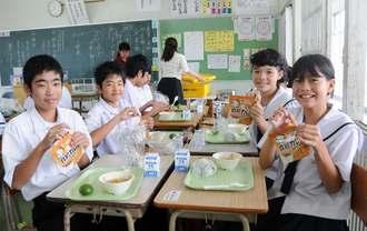 災害時給食用非常食の「救給カレー」のパックを開ける1年4組の生徒たち=1日、南城市・大里中学校